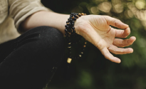 A hand in a meditative mudra with mala beads